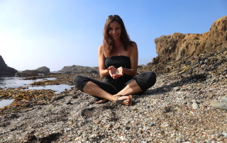 Annette White sitting on Glass Beach in Fort Bragg