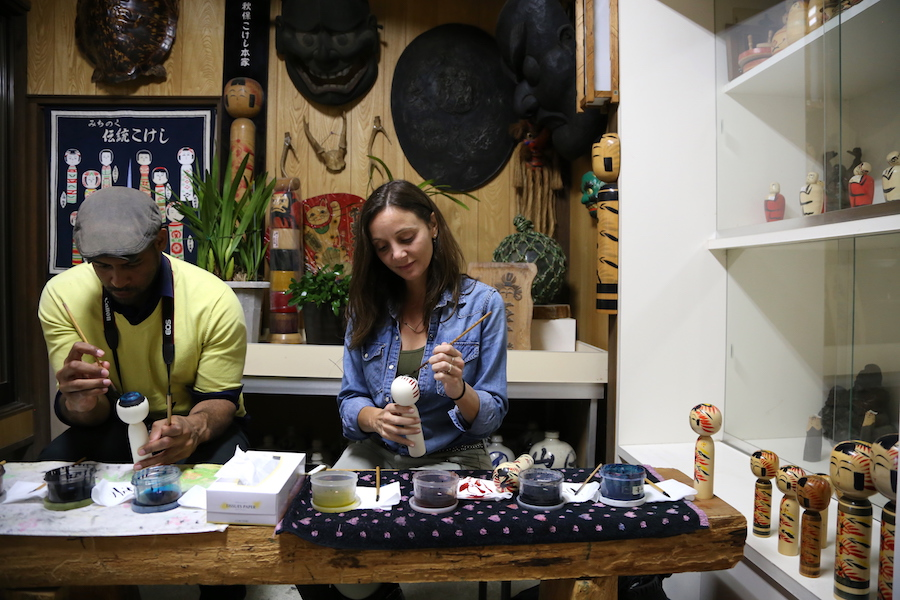 Annette White painting a Kokeshi doll at the Aiku Craft Center in Sendai, Japan