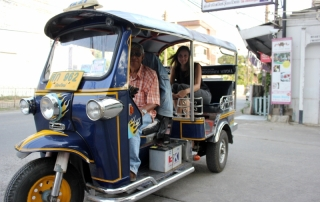 Annette White riding a tuk tuk in Thailand