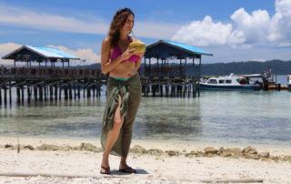 Annette White enjoying a fresh coconut at Arborek Village in Raja Ampat