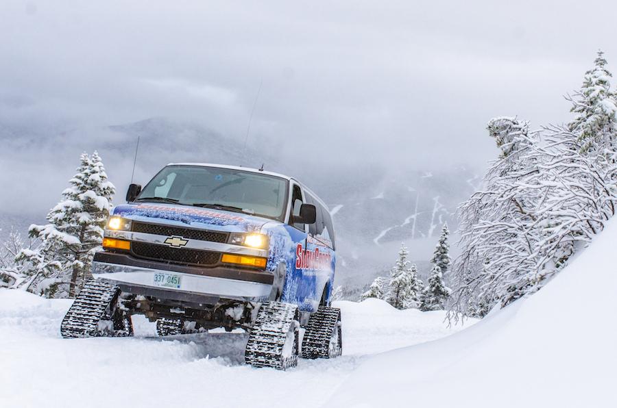 A snowcoach making it's way through winter terrain
