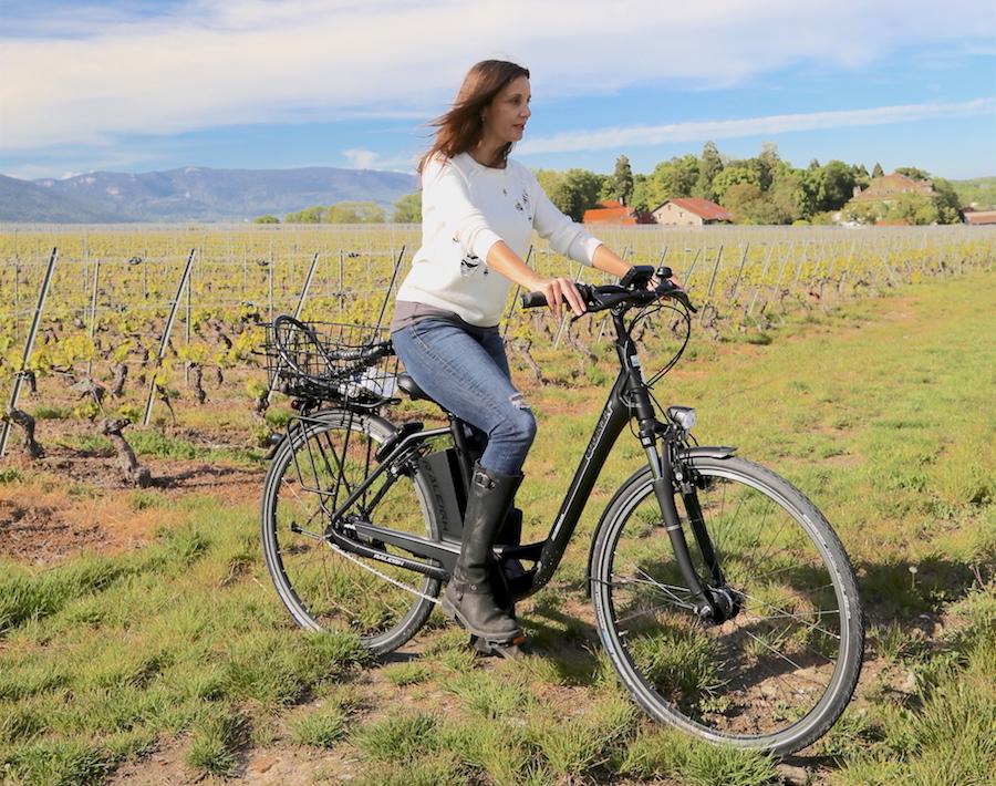 Annette White riding a bike through the vineyards of Geneva Switzerland