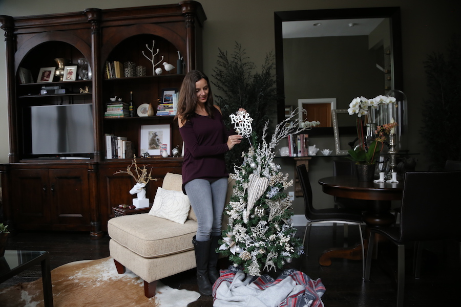 Annette White decorating a donation Christmas tree